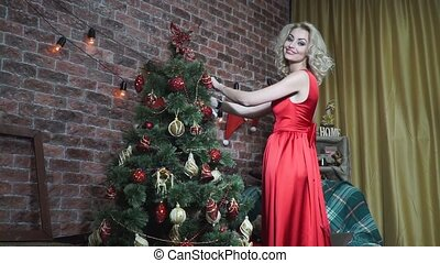 Blonde in a red dress hangs on the Christmas tree toy -...