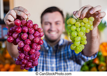 Smiling man selling grapes in shop. - Portrait of smiling...