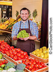 Man offers fresh salad. - Smiling man offers fresh salad in...