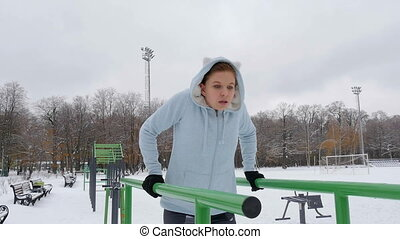 Young girl doing push-ups on the bars. Winter - Young girl...