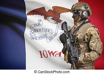 Soldier in helmet holding machine gun with USA state flag on background series - Iowa