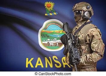 Soldier in helmet holding machine gun with USA state flag on background series - Kansas