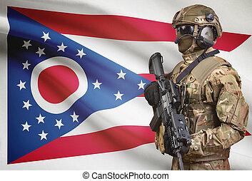 Soldier in helmet holding machine gun with USA state flag on background series - Ohio