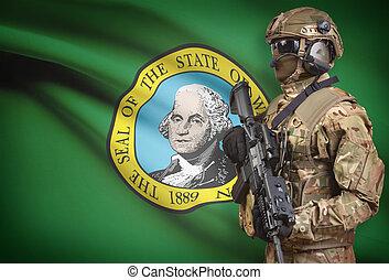 Soldier in helmet holding machine gun with USA state flag on background series - Washington