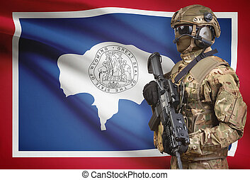 Soldier in helmet holding machine gun with USA state flag on background series - Wyoming