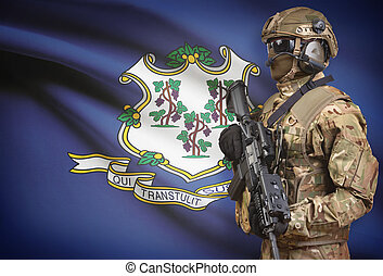 Soldier in helmet holding machine gun with USA state flag on background series - Connecticut