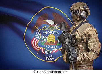 Soldier in helmet holding machine gun with USA state flag on background series - Utah