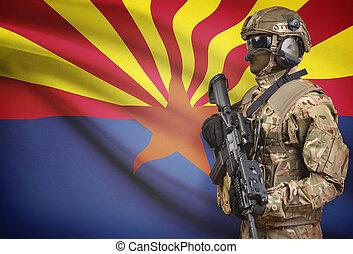 Soldier in helmet holding machine gun with USA state flag on background series - Arizona