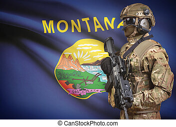 Soldier in helmet holding machine gun with USA state flag on background series - Montana