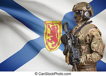 Soldier in helmet holding machine gun with Canadian province...