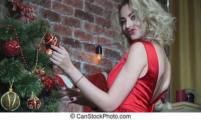 Closeup, seductive blonde girl playing with a toy on the Christmas tree