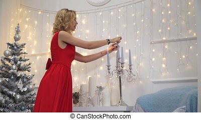 Girl in red dress lights candles in a candlestick -...