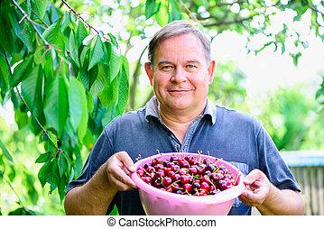 man with cherries in garden
