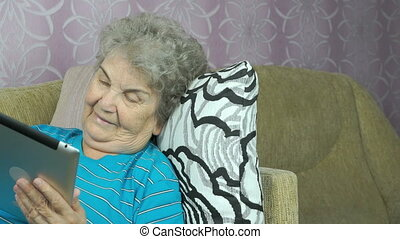 Old woman relaxes using a tablet computer