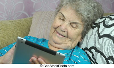 Elderly woman with a tablet computer indoors