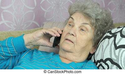 Elderly woman talking with friend on mobile phone - Elderly...