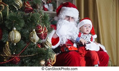 Santa waving from behind a Christmas tree sitting with a baby