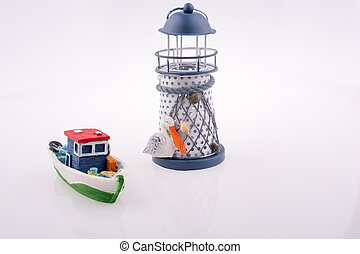 Little colorful model boat and a lighthouse - Little...