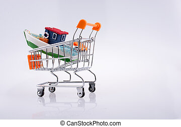 Little colorful model boat in shopping cart on white...