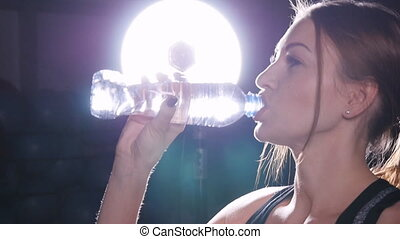 Muscular woman drinking water in crossfit - Muscular woman...