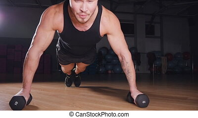 Young muscular athlete doing pushups in gym