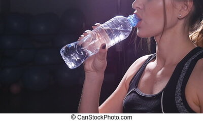 Young fit woman drinking water at gym slow motion