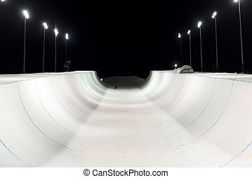 Snowboarder in a snow halfpipe at night lit up by lights -...