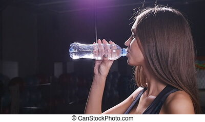 Muscular woman drinking water in crossfit