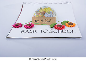 Globe, flowers and back to school title on a white...