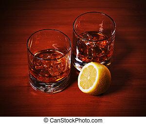 Highball whiskey glass with ice and lemon. - Highball...