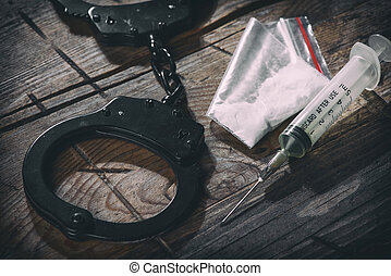 handcuffs and narcotic on a wooden background