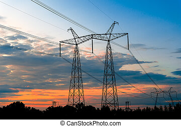 Electrical pylons on the background of the transformer substation during sunset.