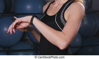 woman with heart-rate watch and smartphone in gym - woman...