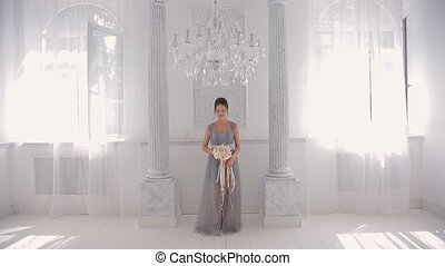 Bridesmaid in gray dress barefoot with bouquet goes directly...