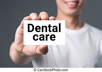 DENTAL CARE message on the card shown by a man