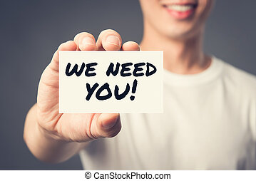 WE NEED YOU! message on the card shown by a man
