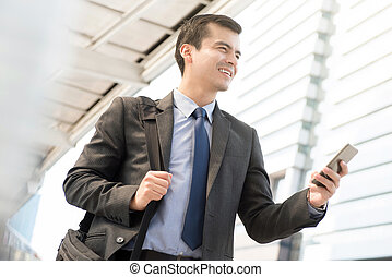 Businessman using mobile phone while walking