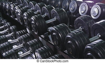 man takes with dumbbell stand - Close up of dumbbells lying...
