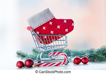 Shopping cart with christmas sock and lolipop on white...