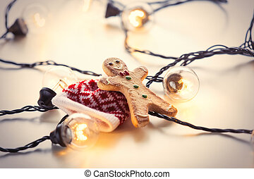 Fairy lights and gingerbread cookie man on white background