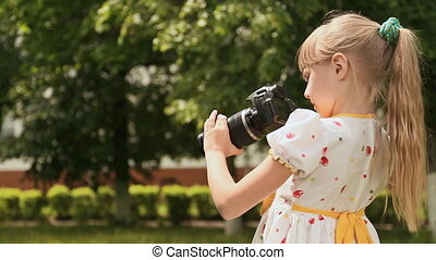 Little girl with camera in a green park.