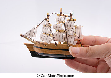Little colorful model boat in hand on white background