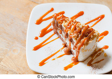 Banoffee pie with caramel sauce on the woden table