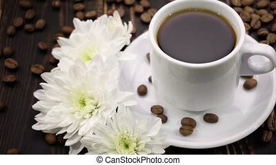 chrysanthemum and coffe on the wooden table - chrysanthemum...