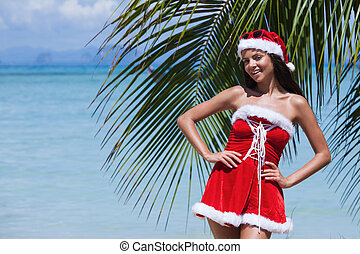 Mrs. Claus on tropical beach - Beautiful woman in Mrs. Claus...