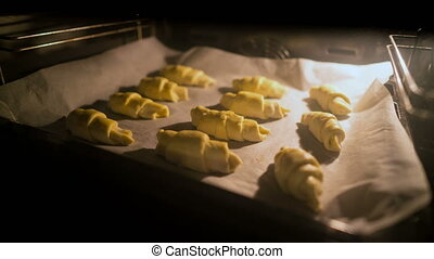 Croissants are baked in the oven. - Croissants are baked in...