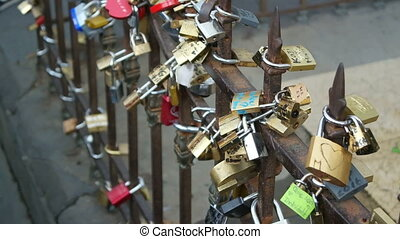 Locks are hanging on fence. Many rusty padlocks. Symbols of...