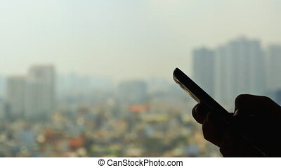 Man dials the phone against the backdrop of the city from the window 1