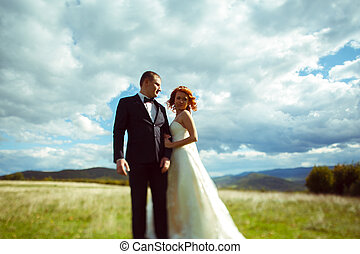 White clouds spread over a stunning wedding couple standing...