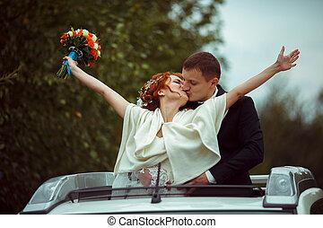 Groom hugs bride from behind standing in an open hatchway
